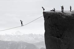 Hommes d'affaires marchant sur la corde au-dessus de la falaise Photo stock