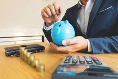 Hommes d'affaires mettant la pièce de monnaie à la tirelire bleue, enregistrant l'argent finan photo libre de droits