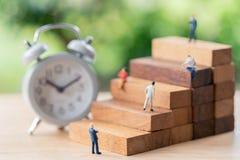 Hommes d'affaires miniatures de personnes tenant l'analyse financière d'investissement ou dedans images libres de droits