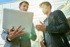 Hommes d'affaires modernes utilisant l'ordinateur portable dehors Photos stock