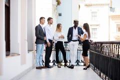 Hommes d'affaires multi-ethniques ayant la pause-café au balcon de l'immeuble de bureaux photo libre de droits