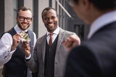 Hommes d'affaires multi-ethniques de sourire de jeunes dans le formalwear se réunissant dehors Images libres de droits