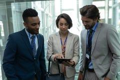 Hommes d'affaires multi-ethniques discutant au-dessus du comprimé numérique dans l'ascenseur de bureau photos stock