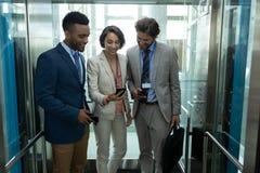 Hommes d'affaires multi-ethniques discutant au-dessus du téléphone portable dans l'ascenseur photo libre de droits
