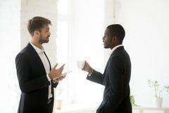 Hommes d'affaires multi-ethniques discutant des stratégies commerciales pendant l'OE photo stock