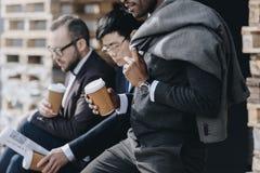 Hommes d'affaires multiculturels tenant les tasses de café de papier et s'asseyant dehors Images stock