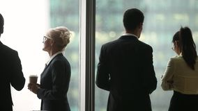 Hommes d'affaires multinationaux de vue de dos parlant la position près de la fenêtre panoramique clips vidéos