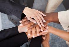Hommes d'affaires multiraciaux empilant des mains image stock