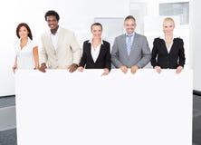 Hommes d'affaires multiraciaux tenant la plaquette photographie stock libre de droits