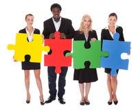 Hommes d'affaires multiraciaux tenant le puzzle denteux photographie stock