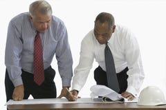 Hommes d'affaires observant des modèles Images libres de droits