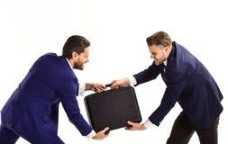 Hommes d'affaires ou hommes dans les costumes classiques tirant la serviette noire Photos stock