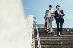 Hommes d'affaires parlant et descendant les étapes image libre de droits