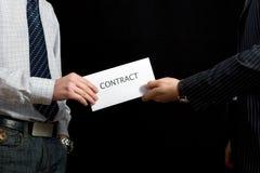 Hommes d'affaires partageant un contrat Images stock