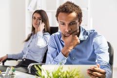 Hommes d'affaires réfléchis travaillant dans le bureau Images stock