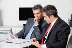 Hommes d'affaires réfléchis utilisant la Tablette de Digital à Photo stock
