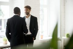 Hommes d'affaires réussis divers se tenant parlants dans le bureau Image stock