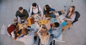 Hommes d'affaires réussis heureux de métis de vue supérieure les jeunes travaillent ensemble au bureau moderne léger, parlant banque de vidéos