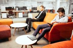 Hommes d'affaires réussis travaillant aux dispositifs photographie stock libre de droits