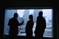 Hommes d'affaires regardant à l'extérieur l'hublot Photographie stock libre de droits