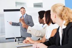Hommes d'affaires regardant l'explication de l'homme Images stock
