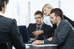 Hommes d'affaires regardant l'ordinateur portatif photographie stock libre de droits