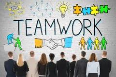 Hommes d'affaires regardant le concept de travail d'équipe sur le mur Images stock