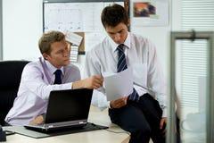 Hommes d'affaires regardant le document dans le bureau Photographie stock libre de droits