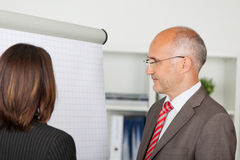 Hommes d'affaires regardant le flipchart Photo stock