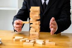 Hommes d'affaires sélectionnant des blocs de dominoe pour remplir dominos absents images stock