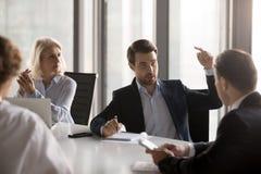 Hommes d'affaires sérieux discutant la nouvelle séance de projet au bureau dedans photographie stock libre de droits