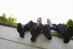 Hommes d'affaires s'asseyant côte à côte sur le mur Photographie stock libre de droits