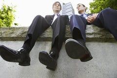 Hommes d'affaires s'asseyant côte à côte sur le mur Photos libres de droits