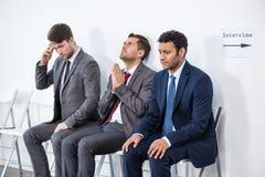 Hommes d'affaires s'asseyant dans la file d'attente et l'entrevue de attente dans le bureau Photos stock