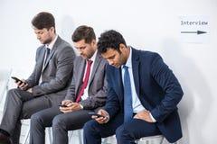 Hommes d'affaires s'asseyant dans la file d'attente et l'entrevue de attente dans le bureau Images libres de droits
