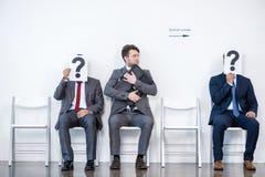Hommes d'affaires s'asseyant dans la file d'attente et l'entrevue de attente, tenant des points d'interrogation dans le bureau Photos stock