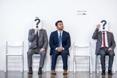 Hommes d'affaires s'asseyant dans la file d'attente et l'entrevue de attente, tenant des points d'interrogation dans le bureau Photographie stock