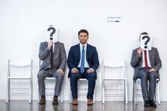 Hommes d'affaires s'asseyant dans la file d'attente et l'entrevue de attente, tenant des points d'interrogation dans le bureau Images libres de droits