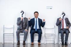Hommes d'affaires s'asseyant dans la file d'attente et l'entrevue de attente, tenant des points d'interrogation dans le bureau Photographie stock libre de droits