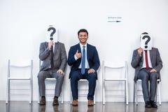 Hommes d'affaires s'asseyant dans la file d'attente et l'entrevue de attente, tenant des points d'interrogation dans le bureau Images stock