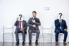 Hommes d'affaires s'asseyant dans la file d'attente et l'entrevue de attente, tenant des points d'interrogation dans le bureau Photos libres de droits