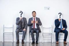 Hommes d'affaires s'asseyant dans la file d'attente et l'entrevue de attente, tenant des points d'interrogation dans le bureau Photo libre de droits