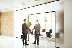 Hommes d'affaires se serrant la main dans l'intérieur Photographie stock