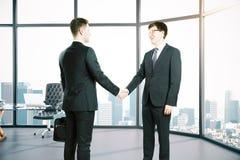 Hommes d'affaires se serrant la main dans la chambre Image stock