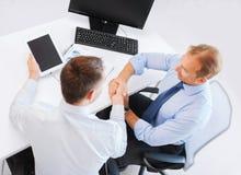 Hommes d'affaires se serrant la main dans le bureau Images libres de droits