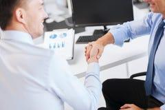 Hommes d'affaires se serrant la main dans le bureau Photographie stock