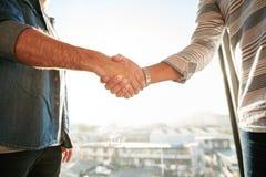 Hommes d'affaires se serrant la main dans le bureau Photos stock