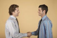 Hommes d'affaires se serrant la main sur le fond coloré Image libre de droits