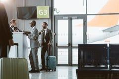 hommes d'affaires se tenant à la réception d'aéroport pour acheter des billets tandis que marche de collègue images stock