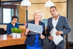 Hommes d'affaires se tenant au compteur de réception Photo stock